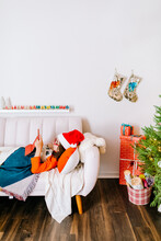 Boy Wearing Santa Hat  Using Tablet Lying In Sofa By Holidays Decoration And Christmas Tree