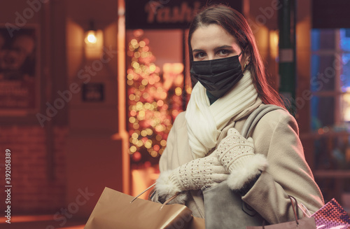 Fotografiet Woman doing Christmas shopping and wearing a protective face mask