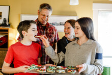 Sister Giving  Decorated Holiday Cookie To Teen Brother