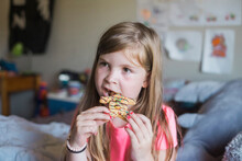 Young Girl Eating A Gingerbread Man In Her Bedroom