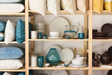 Shelf Display Of Glass And Terra Cotta Plates And Bowls At Home Store