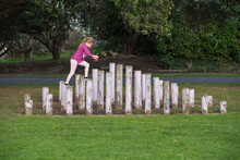 Young Girl Walking And Balancing On Wooden Poles At The Park