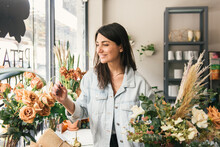 Smiling Woman Picks Roses From...