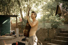 A Topless Man Playing Guitar Outside