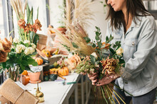 Half Body Crop Of Woman Holding Seasonal Bouquet Of Flowers In Shop