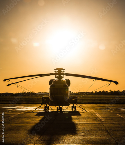 Helicopter on helipad while sun sets