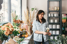 Woman Florist Looking At A Single White Rose She Has Styled In Shop