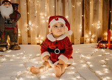 A Little Girl Sitting In A Santa Claus Outfit.