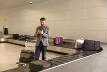 Man Using Smartphone Near Luggage Carousel