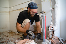 Man Working On The Home Improvement Surrounded By Debris From A Wall