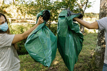 Close-up Of Volunteer Couple Holding Garbage Bags In A Forest.