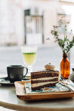 Slice Of Chocolate Cake, Flowers, Cup Of Tea On Table In Outdoors Cafe