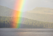 Vivid Rainbow Shining Over Calm Lake With Boat Near Shore With Forest
