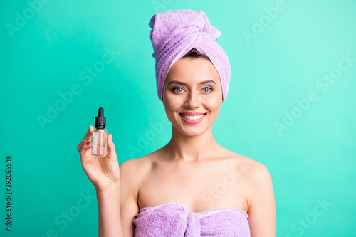 Photo of charming young girl hold bottle dropper toothy smile wear violet towel turban isolated turquoise color background