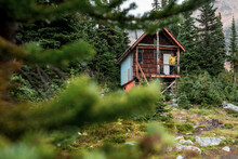 Hiker Man Standing On Porch Of Old House In Forest While Hiking In BC