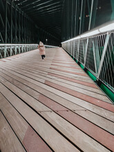 Girl From Behind Walking On A Bridge At Night