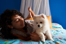A Little Girl Looks At Her White Pomeranian Puppy