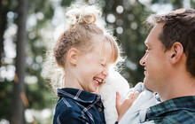 Little Girl Laughing With Her Daddy Carrying Her Smiling At Her