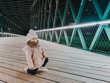 Little Girl With Pacifier Posing On A Bridge At Night