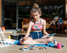 White Girl Painting A Picture Sitting On A Terrace With All Painting Elements Around As Brushes, Paints, Water,..
