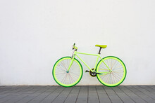 A Green Vintage City Bicycle Fixed Gear On White Wall