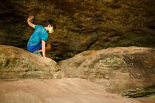 A Boy Crawls Across Boulders Against Rock Wall In Sandstone Gorge