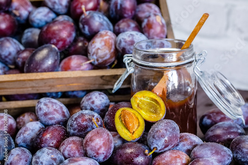 Fotografie, Obraz Wooden crate with plums and plum jam in a jar on a wooden table.