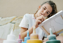 White Girl Painting With A Brush Her Picture In Front Of Bottle Paintings. Horizontal Photo