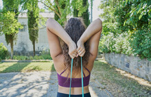 Back View Of A Young Woman Practicing Calisthenic With An Elastic Band