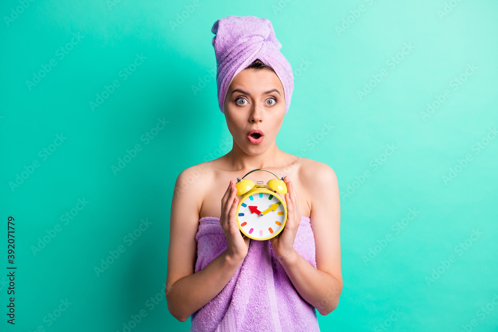 Fototapeta Photo of stupored lady hold alarm clock miss morning spa salon procedure wear towels isolated teal color background