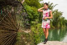 Beautiful Woman Standing Next To Water Mill In Yangshuo
