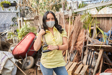 Young Woman With A Face Mask Doing Garden Work