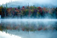 Early Morning Fog Rising Above Calm Lake In The White Mountains Of NH.