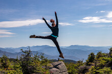 Young Woman Jumping Off Rock A...