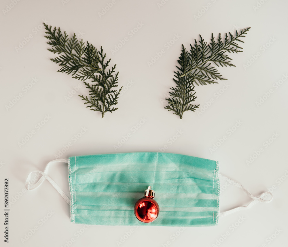 Fototapeta Creative and minimal coronavirus christmas concept. Reindeer face made of Christmas decoration and pine branches with mask on white backgroud. Covid during Christmas season concept. Flat lay top view.