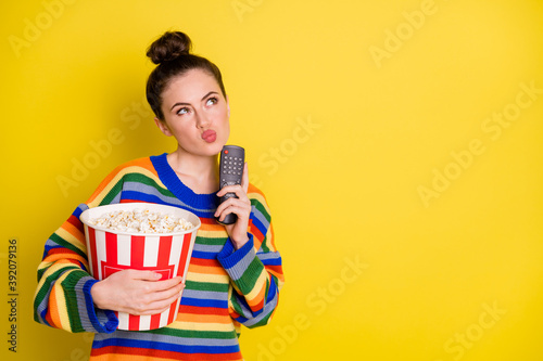 Obraz Photo of young attractive woman think hold remote control eat pop-corn look empty space isolated over yellow color background - fototapety do salonu