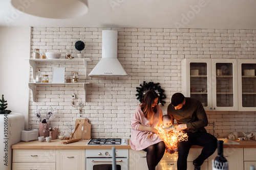 Fototapeta Young parents sit with little daughter at the kitchen, lovely family with cute t