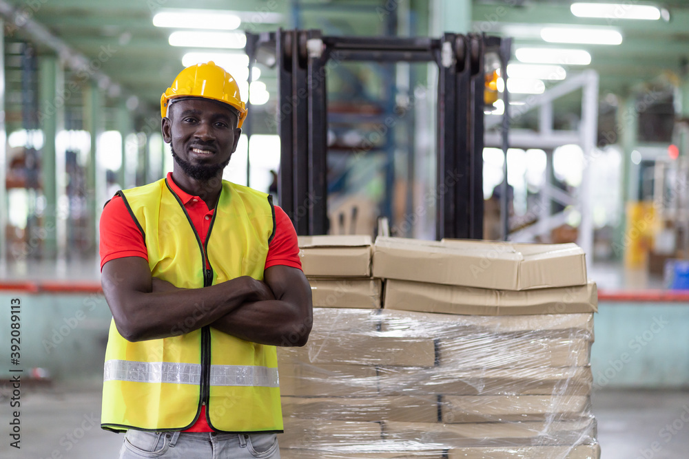 Leinwandbild Motiv - amorn : Confident smiling African American male warehouse worker in safety vest and helmet standing with arms crossed in automotive spare parts storage warehouse over parcel stack on forklift truck