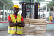 Leinwandbild Motiv Confident smiling African American male warehouse worker in safety vest and helmet standing with arms crossed in automotive spare parts storage warehouse over parcel stack on forklift truck