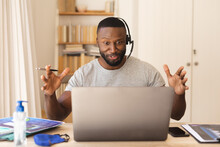 African American Man Using Phone Headset While Having A Video Chat On Laptop While Working From Home