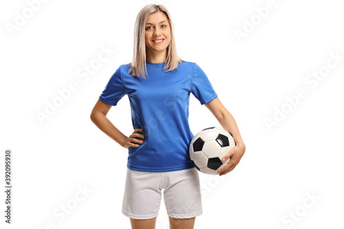 Obraz Female soccer player smiling and posing with a soccer ball under her arm - fototapety do salonu