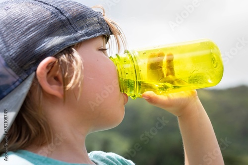 Fotografie, Obraz Active thirsty kid drinking water outdoor. Hydration.