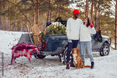 Multiracial couple in white sweatshirts stand with a dog near a car in the forest.