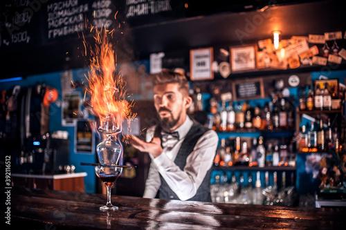 Obraz Bartender makes a cocktail behind the bar - fototapety do salonu