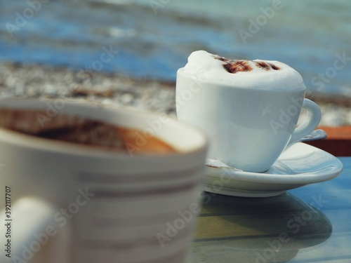 Papel de parede Two cups with cappuccino are on the table of a summer cafe by the sea