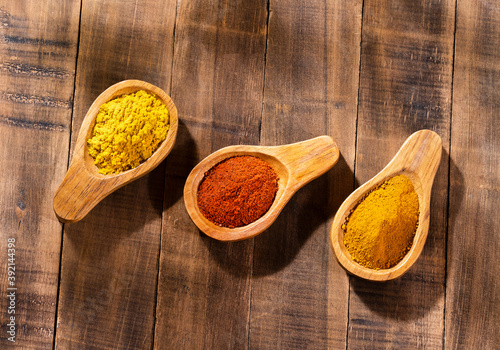 Curry, turmeric and paprika spices in the wooden spoons Fotobehang