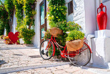 Classical Bicycle Parked In The Middle Of The Old Town Surrounded With Flowers And Trafitional Greece, Italian Style.