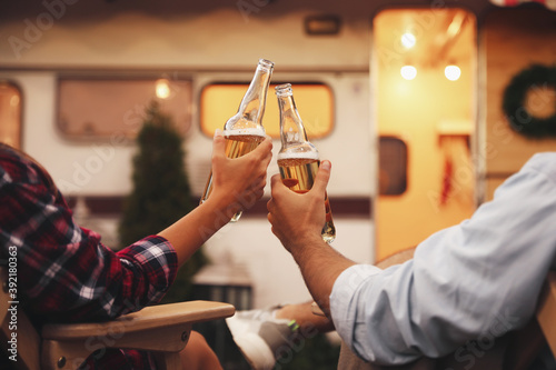 Fotografering Young couple toasting with bottles of beer near trailer, closeup