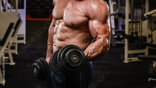 Photo strong physique body of muscle male training pumping biceps with iron heavy dumb