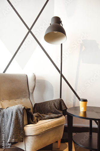 Fotografia a soft, large gray armchair against an avant-garde wall, a coffee table with a y